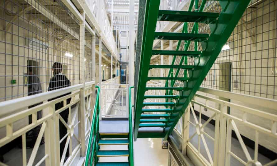 A prisoner is escorted to his cell by an officer next to the stairs
