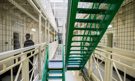A prisoner is escorted to his cell by an officer next to the stairs on Benbow wing inside HMP/YOI Portland