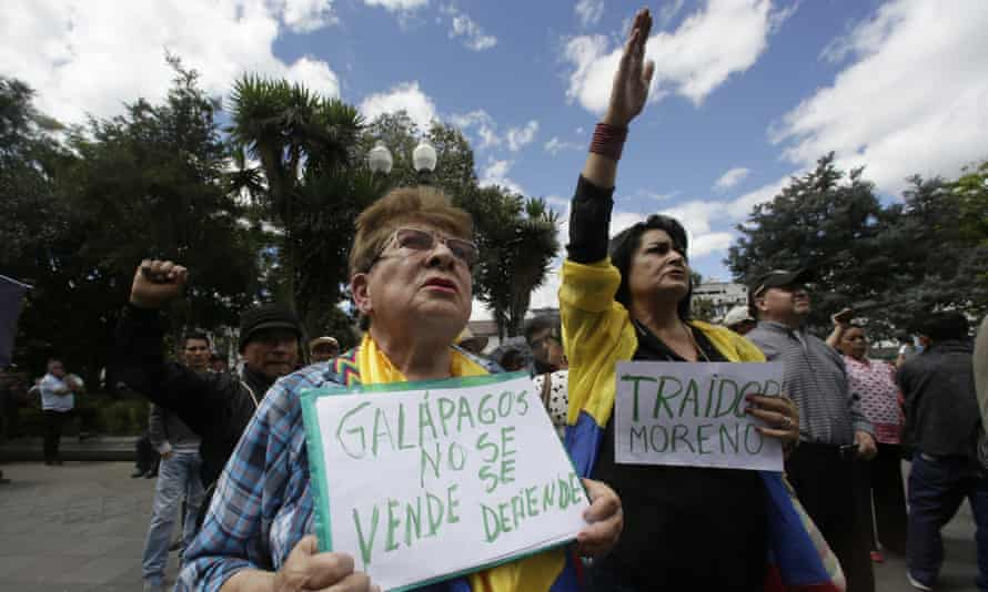 A woman holds a sign that reads in Spanish 'Galápagos is not to be sold, but to be defended' during a protest agains plans to allow the US military to use an island.