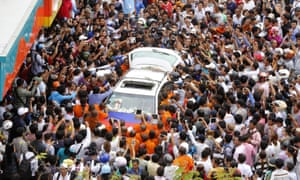 Bystanders take photos of the car carrying the body of political analyst Kem Ley.