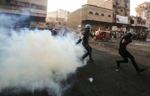 An Iraqi protester returns a teargas canister thrown by security forces during clashes in the capital's Khallani square during anti-government demonstrations.