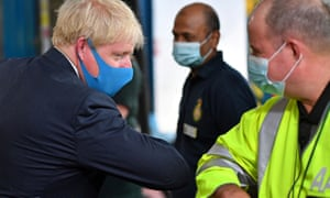 Boris Johnson gives an elbow bump greeting as he visits headquarters of the London Ambulance Service NHS Trust