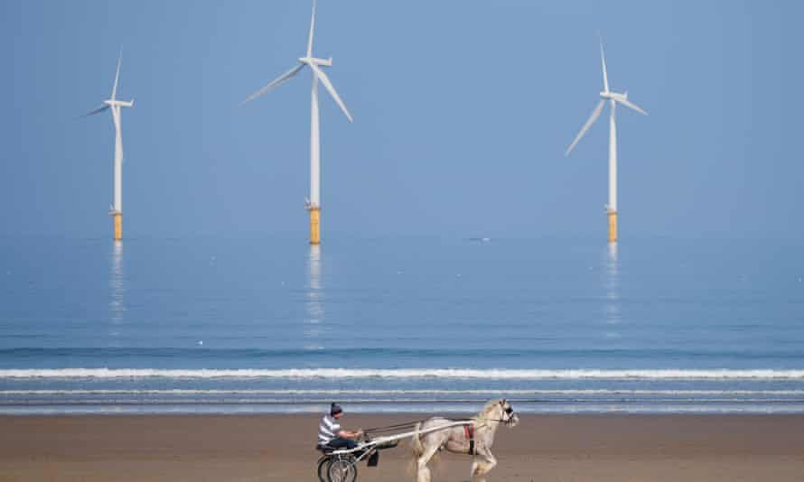 A man rides his horse and trap along the beach in front of the EDF energy windfarm at Redcar, northern England.