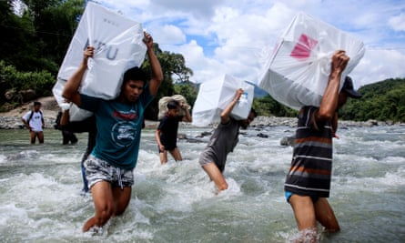 Indonesian election workers carry ballot boxes as they cross a river to deliver them to remote villages in Maros, South Sulawesi
