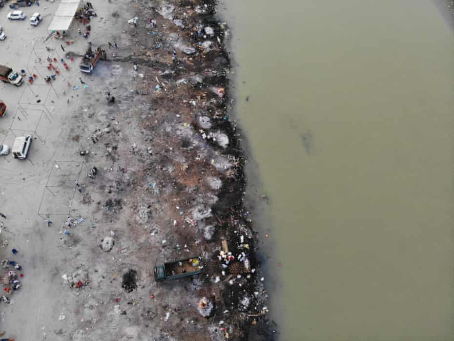 Funeral pyres of coronavirus victims line a bank of the river
