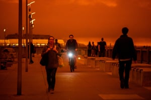 People walk and ride along Embarcadero as smoky skies cover San Francisco.