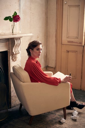 A side view of Vicky sitting in an armchair with a pen and notepad in her hands, wearing a dress by Joseph and shoes by Jimmy Choo.