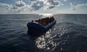 "Migrants and refugees seated on a rubber boat wait to be evacuated during a rescue operation by the crew of the Topaz Responder, a rescue ship run by Maltese NGO ""Moas"" and the Italian Red Cross, on November 4, 2016 off the Libyan coast."