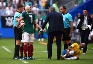Brazil's Neymar reacts as he holds his leg while Mexico's Miguel Layun looks on.