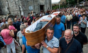 The faithful who consider themselves saved from death by the Santa Marta are carried in coffins during the procession