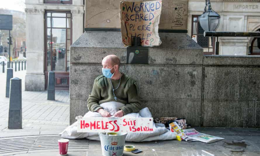 A homeless man sits against a wall in Westminster near Downing Street with a sign that reads 'Homeless Self Isolating' during England's first lockdown in April.