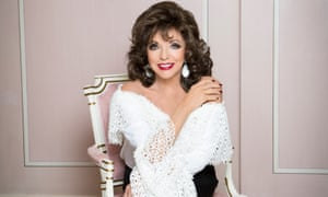 Joan Collins sitting in a white antique chair with pale pink upholstery, matching walls behind her, wearing a white shawl and earrings