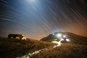 Star trails curves across the sky above small tents.