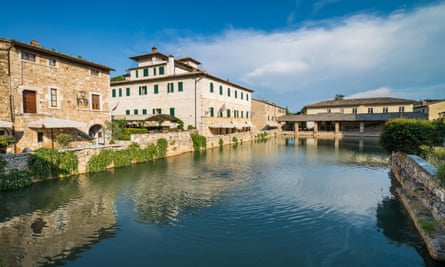 Historic houses by the river, in the foreground, in the village of Bagno Vignoni, Tuscany, Italy