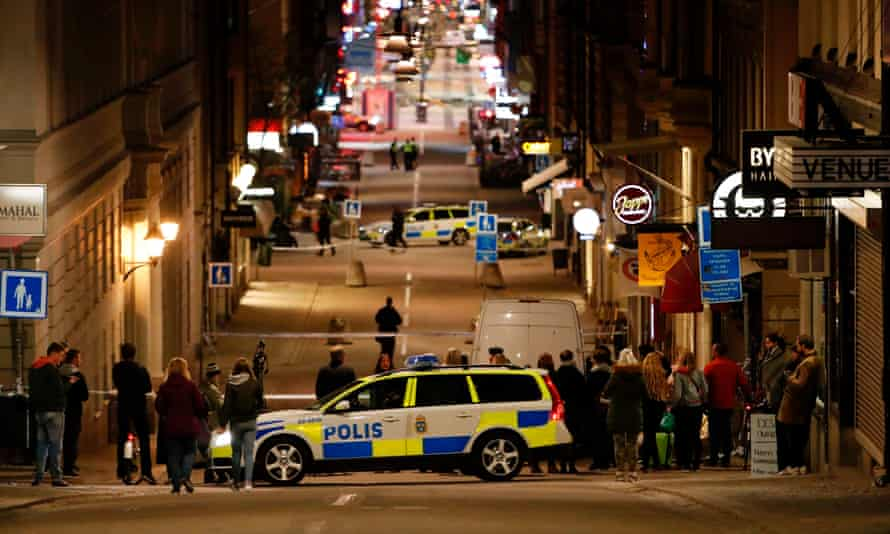People stand behind the police cordon around the scene of the attack.