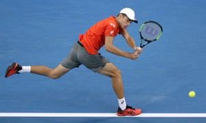 Alex de Minaur makes a backhand return to Rafael Nadal.