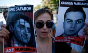 An Armenian protester holds pictures of Ramil Safarov, left, and Gurgen Margaryan during a demonstration outside the Hungarian embassy in Nicosia, Cyprus, in 2012