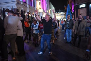People are seen dancing to a busker in Leicester Square on 12 September, 2020 in London, England. From Monday, 14 September, groups of more than six will be banned from meeting under new coronavirus restrictions.