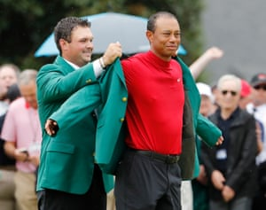 Reed helps Woods into his fifth green jacket.