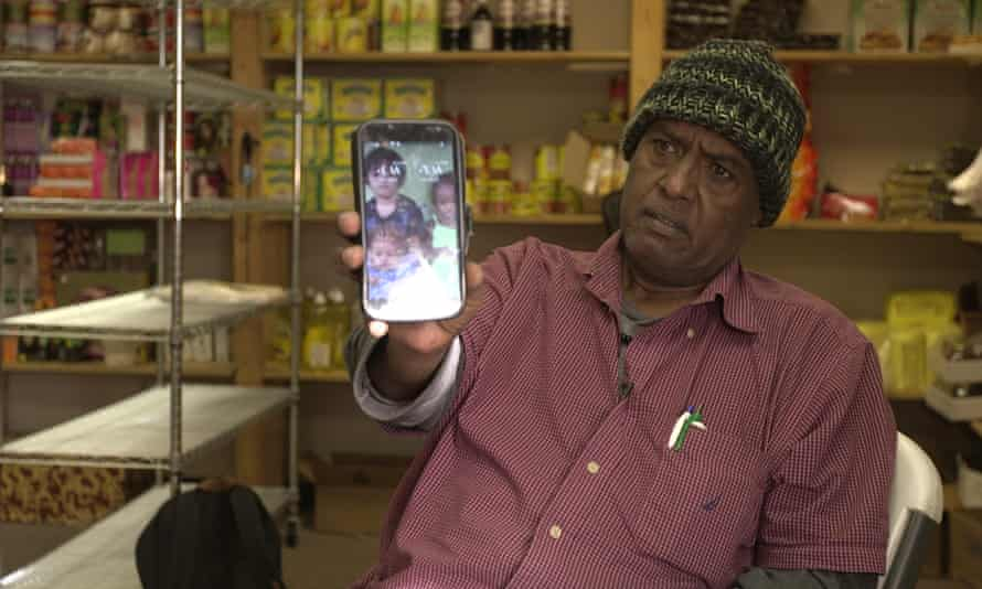 Abdishakur Mohamed Noor shows a photo of children on his cellphone. He hopes they can join him in the US one day.