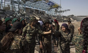 Members of the Syrian Democratic Forces celebrate at a stadium that was the site of Islamic State fighters' last stand in the city of Raqqa.