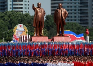 People carry flags in front of floats bearing statues of Kim Il-sung and Kim Jong-il