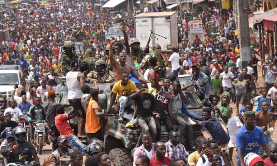People celebrate in the streets of Conakry with members of Guinea's armed forces after the arrest of Alpha Condé.