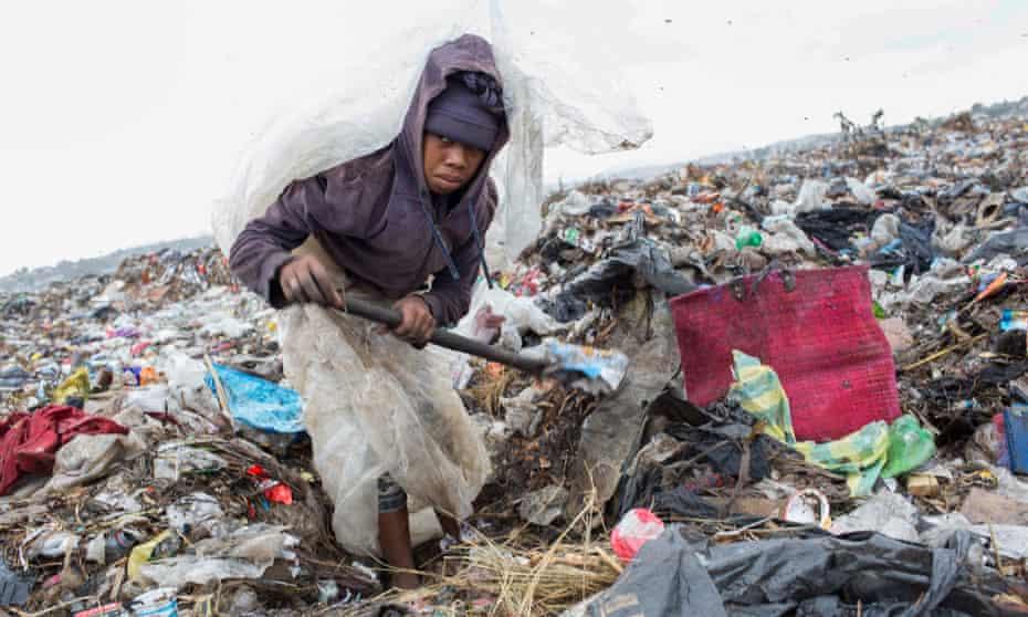 Fanja Randriamihavo, 15, sifts through rubbish at Ralalitra during heavy rain