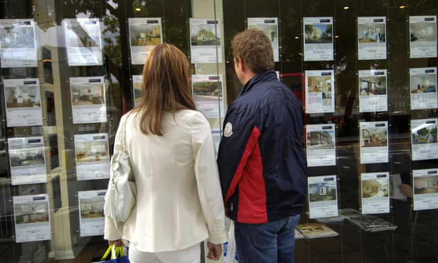 A couple looking at properties in an estate agent's window