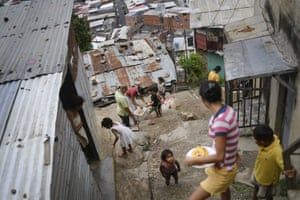 Residents hand out cornmeal cakes known locally as arepas, in the Altos de Lidice community of Caracas amid the coronavirus pandemic