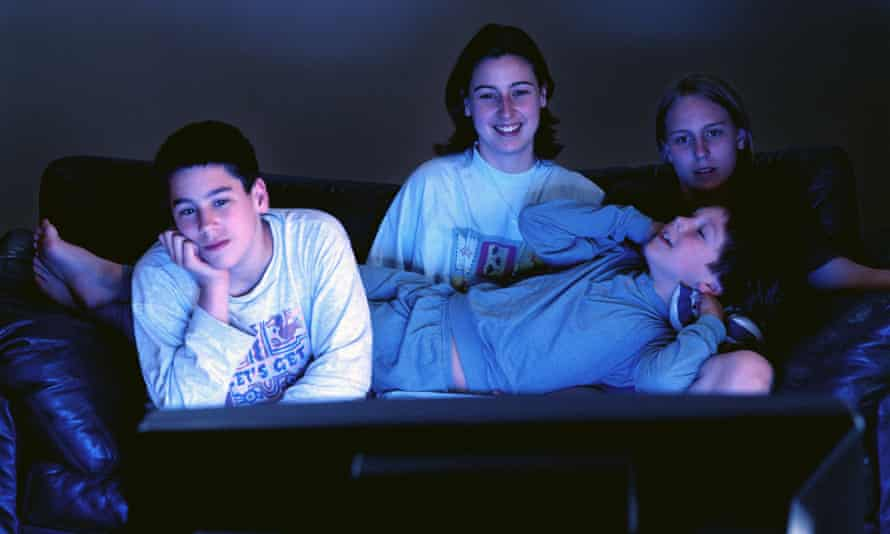 Young adults sitting together on couch watching television in the dark.