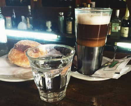 Cup of coffee and glass of water on the bar at El Simbolo, Buenos Aires, Argentina