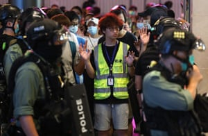 A reporter raises his hands as he is detained with protesters in Causeway Bay