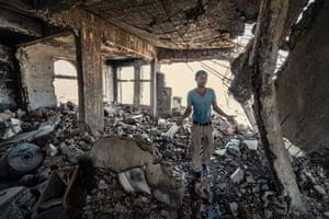 A man walks through his destroyed home in the Al Gamalia neighbourhood in Taiz city, in December 2020