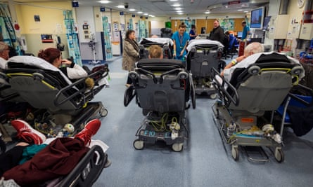 Patients on trolleys wait for attention at an NHS A&E department.