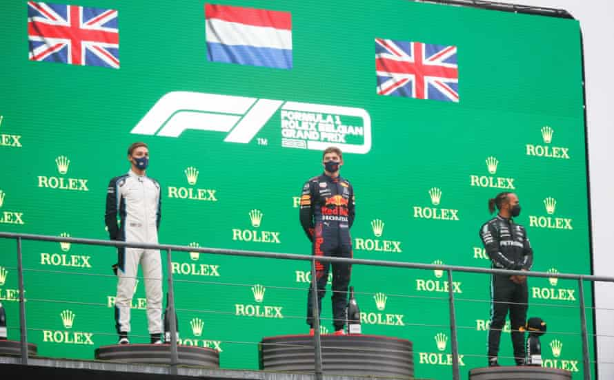 Max Verstappen on the podium as winner, flanked by the second-placed George Russell and Lewis Hamilton