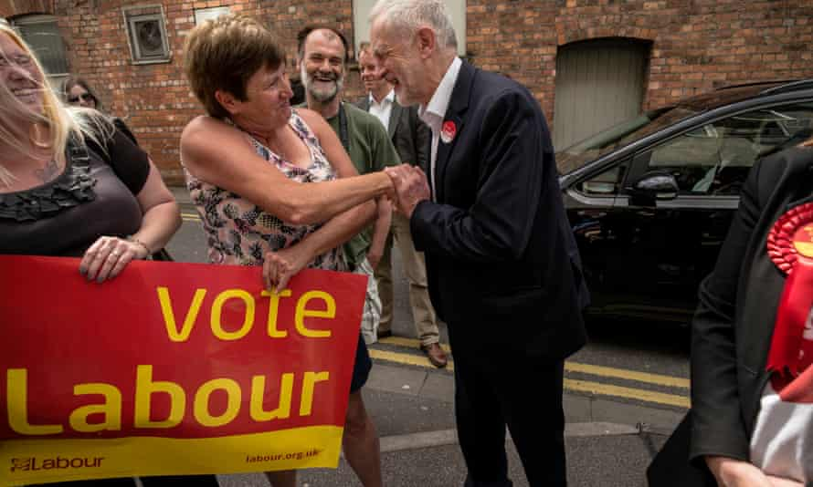 Two women carrying Vote Labour banner, one shaking hands with Jeremy Corbyn
