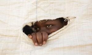 A Zimbabwean secondary school girl peeps through a hole in a sack that is used as a wall of a makeshift classroom