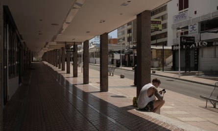 A man sits in an empty street in Magaluf.