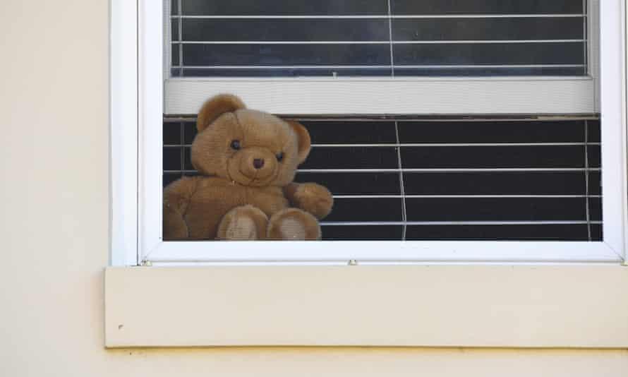 A teddy bear sits inside a window