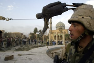 Iraqi civilians and US soldiers pull down a statue of Saddam Hussein in downtown Baghdad, on 9 April 2003.