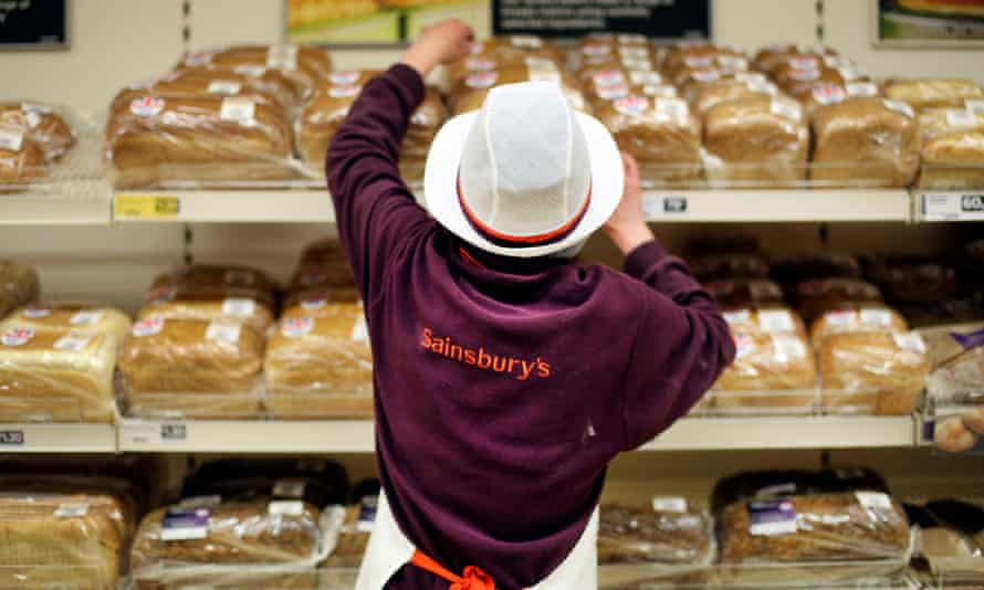 A Sainsbury's worker replenishes the bread aisle