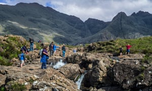 Tourists at the fairy pools, a group of waterfalls in Glen Brittle on the Isle of Skye