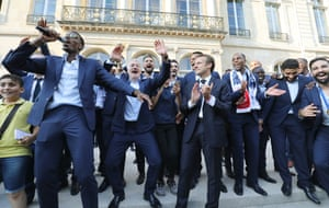 France's midfielder Paul Pogba (L) speaks next to French President Emmanuel Macron (C) and France's coach Didier Deschamps (2ndL) during a reception at the Elysee Presidential Palace in Paris