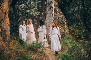 Four girls in white walking through the bush