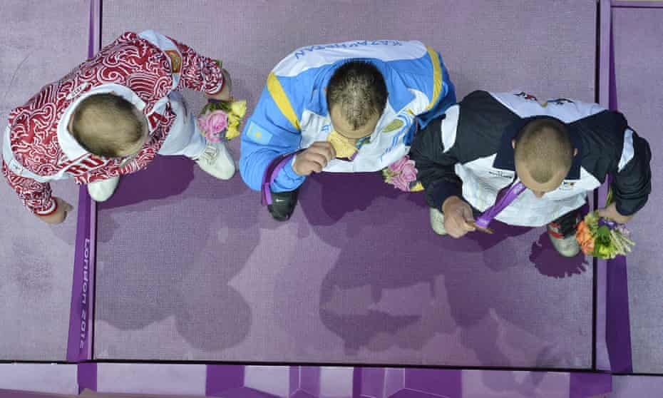 Kazakhstan's Ilya Ilyin (centre) on the podium with his gold medal, Russia's Alexandr Ivanov (left), silver, and Moldova's Anatoli Ciricu, bronze, after the weightlifting 94kg division at London 2012; they were later stripped of their medals.