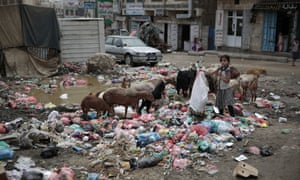 A girl scavenges for recyclable items at a garbage dump in a street in Sanaa, Yemen.