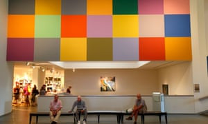 Multicoloured artwork and visitors sat on a bench below it at the Portland Museum of Art, Maine, USA.