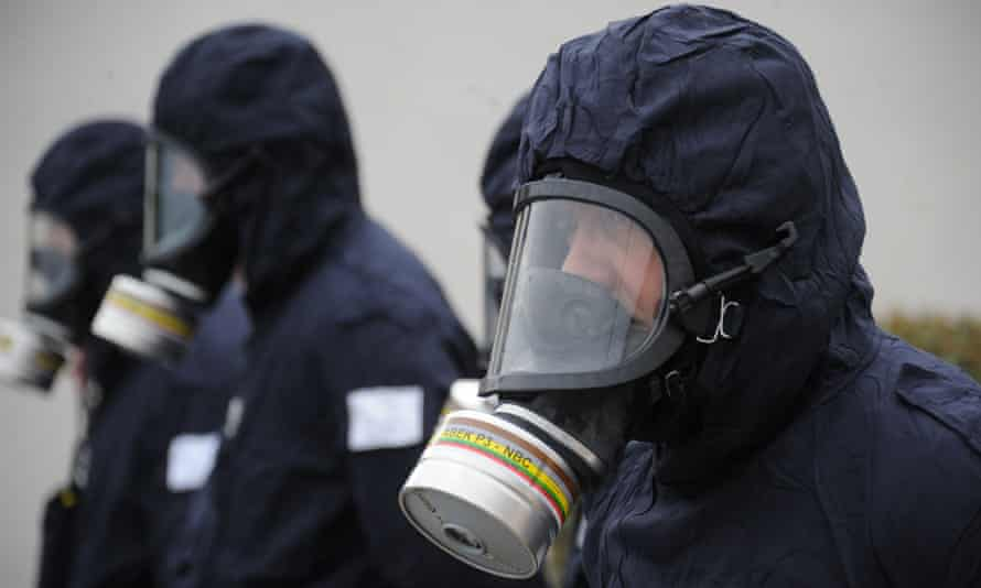 Police officers wearing gas masks