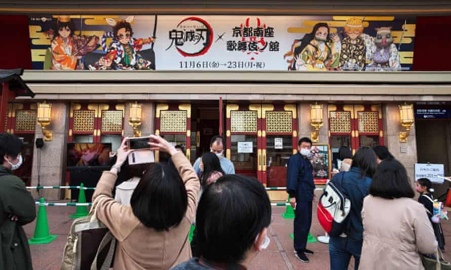 People take photos outside an exhibition about Demon Slayer in Kyoto, Japan